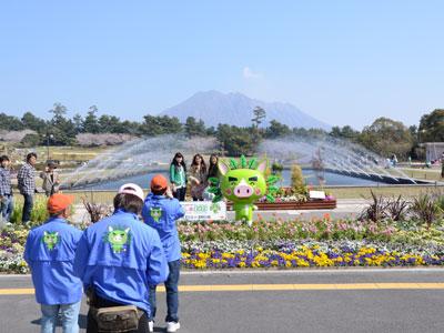 桜島を背景にマスコット「ぐりぶー」と記念写真
