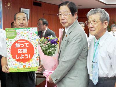 被災地産の花束を手に鹿野農水大臣(中央)。(右)は都倉会長